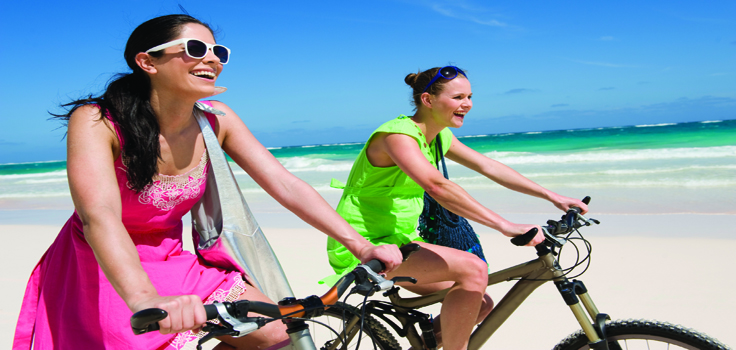 Young women cycling on a beach